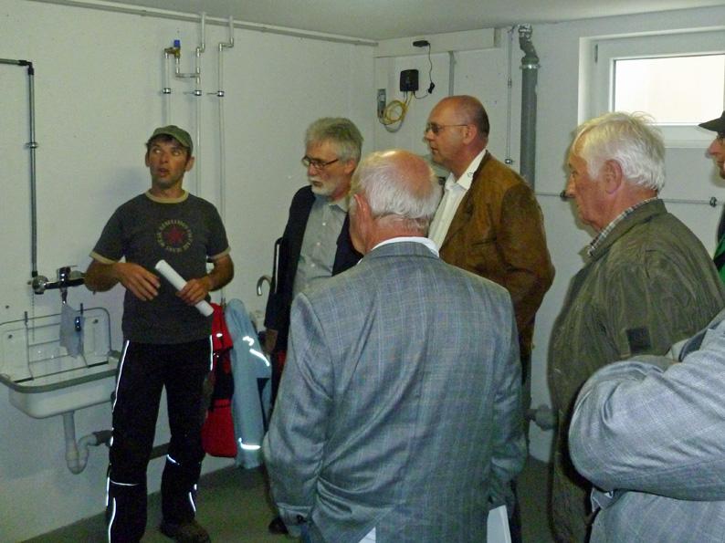 Norbert Weber stellt der Besichtigungsgruppe die Nutzung der Fernwärme, welche aus seiner Biogasanlage gewonnen wird, in einer Heizanlage vor.