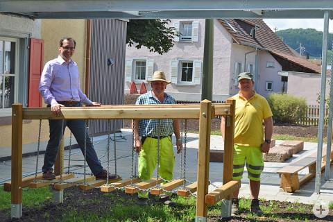 Bürgermeister Martin Numberger, Merbert Maier und Bernd Weber stehen hinter einem Spielgerät.