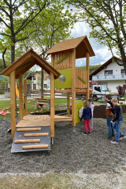 Neue Spielhaus mit zwei Türmen, daneben stehen vier Kinder.