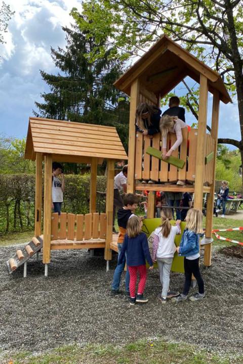 Neue Spielhaus mit zwei Türmen, daneben stehen vier Kinder und im Spielhaus sind weiter Kinder.