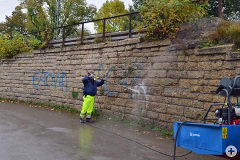 Ein Mitarbeiter des Bauhof Geisingen säubert mit einem Hochdruckreiniger eine mit Graffiti verschmierte Wand.