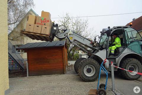 Ein Mitarbeiter vom Bauhof Geisingen hebt mit dem Radlader die Umzugskartons nach oben.