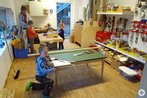 Im Vordergrund sägt ein Kind an einem Tisch mit einer Laubsäge etwas aus. Weiter Kinder sind in der Holzwerkstatt am Basteln.