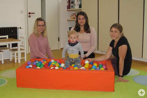 Kindergartenleiterin Patricia Stania, Erzieherinnen Bianca Burkart und Carina Turbanisch sowie Krippenkind Luca im Bällebad.